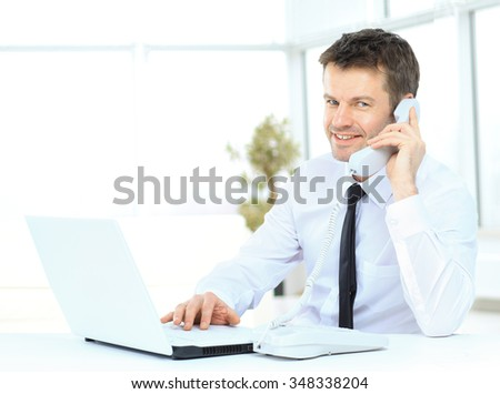 businessman working at the computer talking on the phone and smiling - stock photo