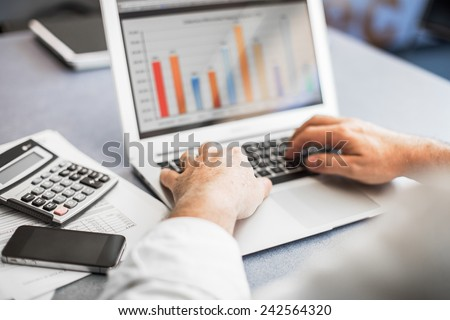 Businessman working in his laptop in a modern office. - stock photo
