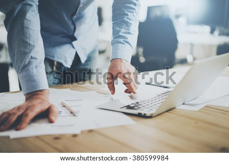 Businessman working in modern cretive studio. Using generic design laptop. Architectural project on table. Blurred background, horizontal mockup. - stock photo