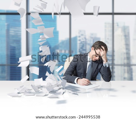 businessman working in office and falling tax papers - stock photo