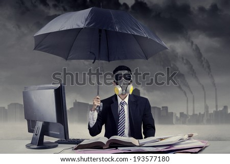 Businessman working in situation of air pollution by using a gas mask and an umbrella - stock photo