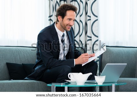 Businessman working in the hotel, he using wifi to read emails with the computer