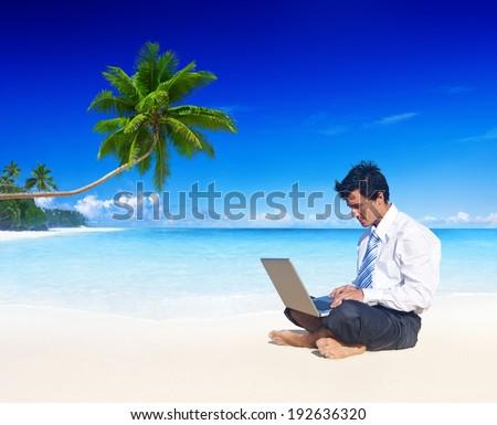 Businessman working on a beach. - stock photo