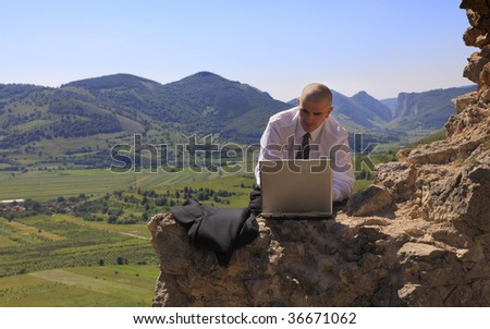 Businessman working on a computer outdoors.