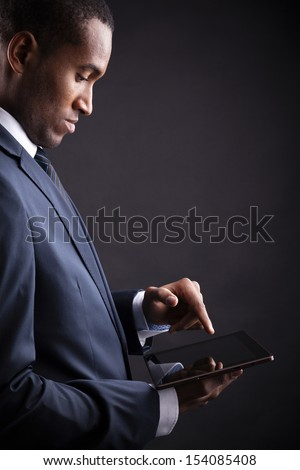 Businessman working on a digital tablet against black background