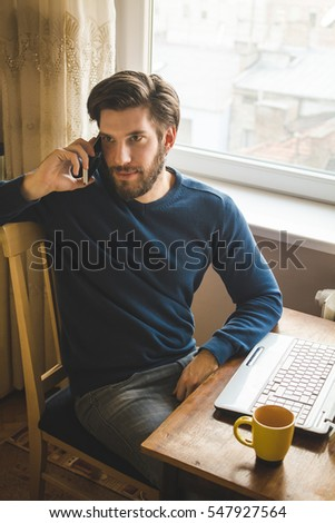 Businessman working on a laptop and using phone