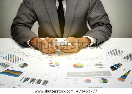 businessman working on cell phone over business report papers,data,statistic