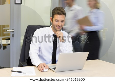 Businessman working on computer in office, business people moving behind him - stock photo