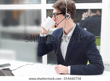 Businessman working on computer with documents. Support service. Business man using laptop on table in with a cup of coffee. Close up. Drink a cup of coffee. Working in the office. - stock photo