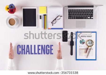 Businessman working on desk - hands showing CHALLENGE concept - stock photo