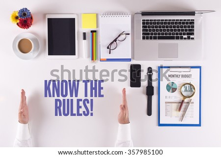 Businessman working on desk - hands showing KNOW THE RULES! concept