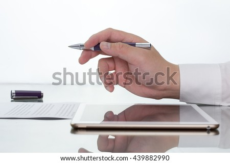 Businessman working on digital tablet on his desk with hand holding pen reflection. - stock photo