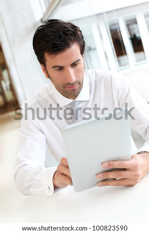 Businessman working on electronic tablet - stock photo