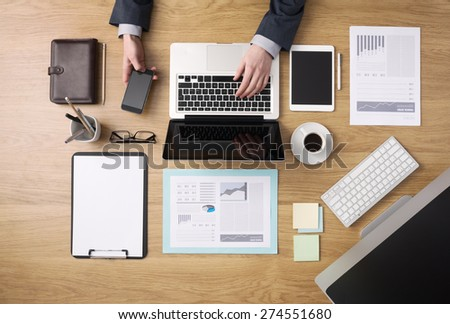 Businessman working on his laptop and using a mobile phone with paperwork and financial reports around, desktop top view - stock photo