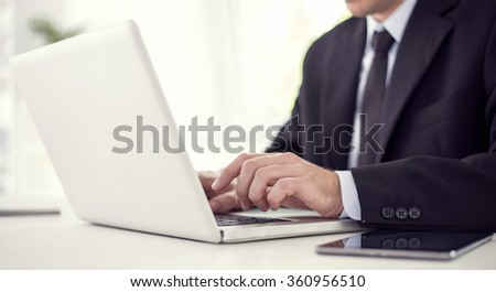 Businessman working on his laptop in the office. He is wearing a black suit and a black tie.Selective focus on his hand. - stock photo