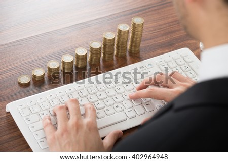 Businessman Working On Keyboard With Coins Stacked - stock photo