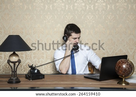 businessman working on laptop and talking on the phone - stock photo