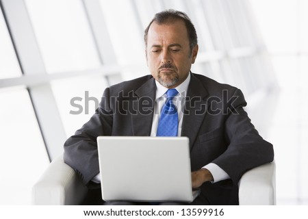 Businessman working on laptop in office lobby - stock photo