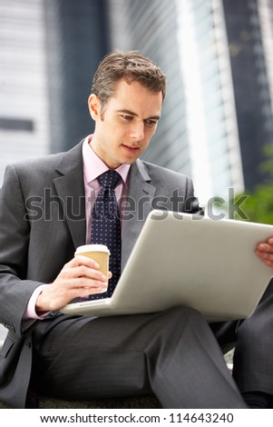 Businessman Working On Laptop Outside Office With Takeaway Coffee - stock photo