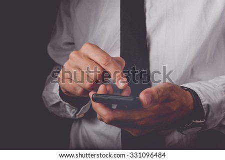 Businessman working on mobile smart phone, finger on touch screen of wireless device, retro toned image, selective focus - stock photo
