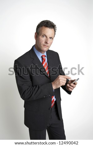 Businessman working on PDA, whilst looking to camera - stock photo