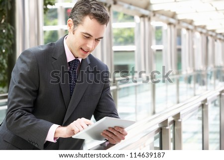 Businessman Working On Tablet Computer Outside Office