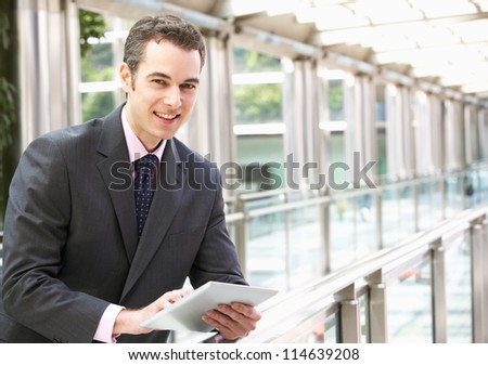 Businessman Working On Tablet Computer Outside Office - stock photo