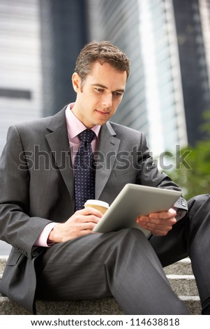 Businessman Working On Tablet Computer Outside Office With Takeaway Coffee - stock photo