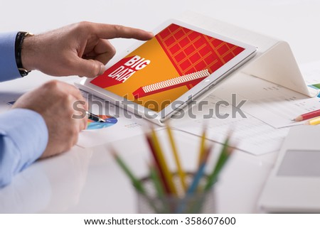 Businessman working on tablet with BIG DATA on a screen - stock photo