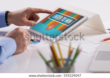 Businessman working on tablet with ENTER TO WIN on a screen