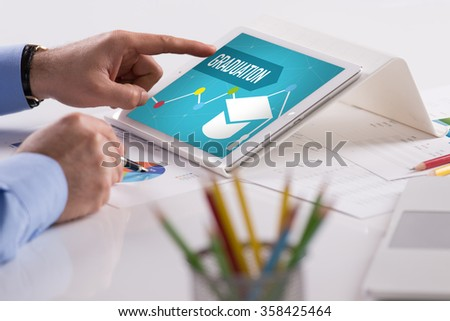 Businessman working on tablet with GRADUATION on a screen - stock photo