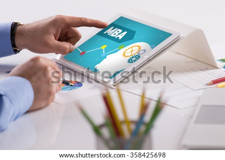 Businessman working on tablet with MBA on a screen - stock photo