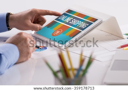 Businessman working on tablet with ONLINE SHOPPING on a screen