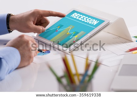 Businessman working on tablet with RECESSION on a screen - stock photo