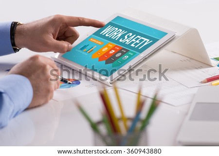 Businessman working on tablet with WORK SAFETY on a screen - stock photo