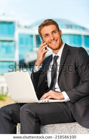 Businessman working outdoors. Handsome young man in formalwear working on laptop and talking on the mobile phone while sitting outdoors and against building structure - stock photo