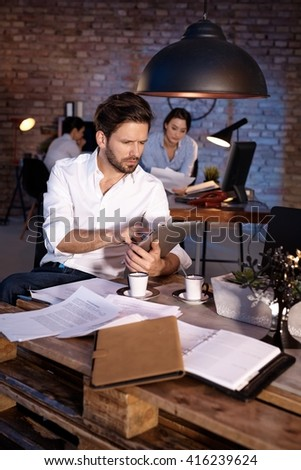 Businessman working overtime in office, using tablet computer.