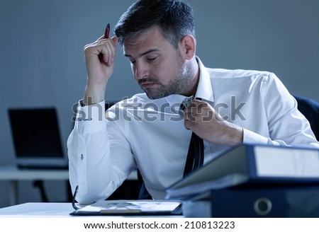 Businessman working overtime in the office, horizontal