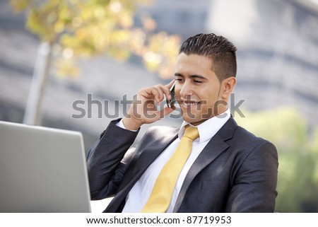 Businessman working sited in a bench at the city park - stock photo