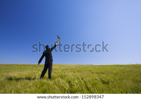 Businessman working with a laptop outdoor on a field
