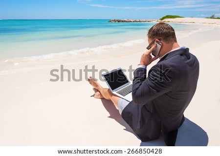 Businessman working with computer and talking on phone on the beach - stock photo