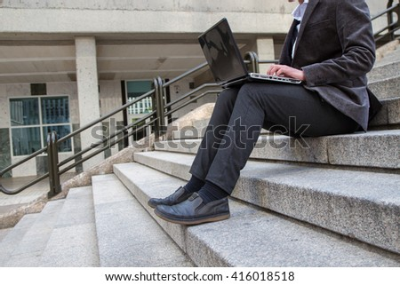 Businessman working with computer on the steps of their work on a break.  - stock photo