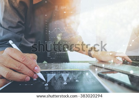 businessman working with digital laptop computer and smart phone with financial business strategy layer effect on wooden desk as concept - stock photo