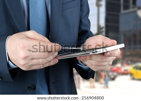Businessman working with digital tablet outside - stock photo