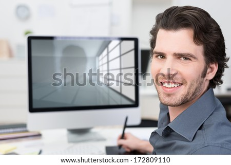 Businessman working with his computer using a tablet and stylus turning away from the visible screen to smile at the camera - stock photo