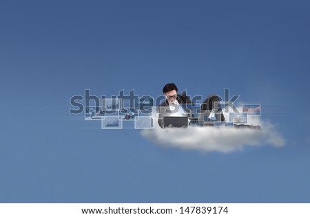 Businessman working with his laptop on a cloud - stock photo