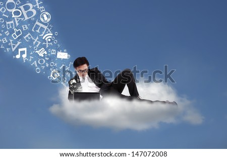Businessman working with his laptop with flying alphabet on cloud - stock photo