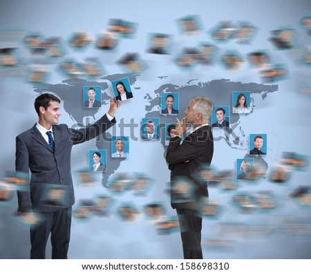 Businessman working with his partner holding picture on map background - stock photo