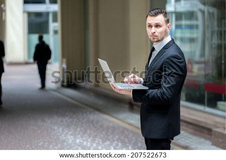 Businessman working with laptop. Businessman talking with a newspaper in his hands forward within an office building. Young business in formal dress