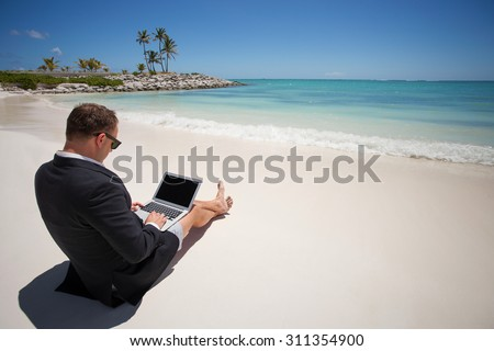 Businessman working with laptop computer on the beach - stock photo